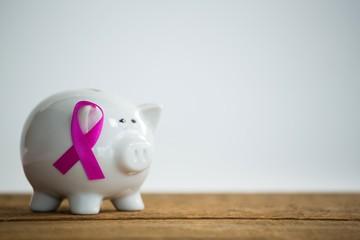 Close-up of pink Breast Cancer Awareness ribbon on piggybank