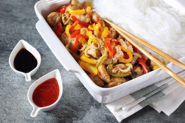 Asian food: fried chicken with bell peppers and rice vermicelli in ceramic crockery, sauces and chopsticks