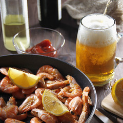 Beer pouring in glass and pan filled with appetizing red shrimps