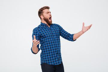 Young attractive bearded man singing loud Fotobehang