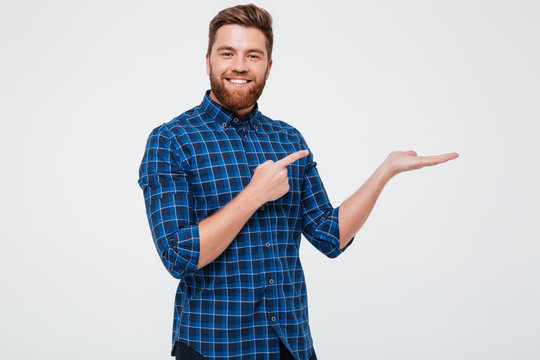 Excited smiling bearded man pointing finger