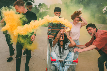 Teenagers having fun with a shopping cart and smoke grenade