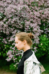 Portrait of young woman among lilac
