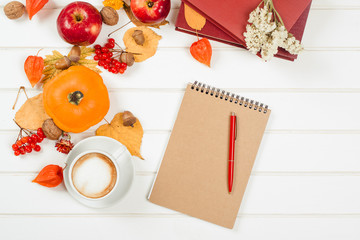 Autumn background, cup of cappuccino, notebook with red pen.