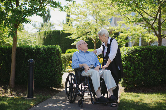 Tender moment between senior couple outside together with wheelchair