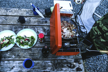 Overhead view of man preparing food on barbeque at campsite