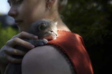Side view of woman embracing cat