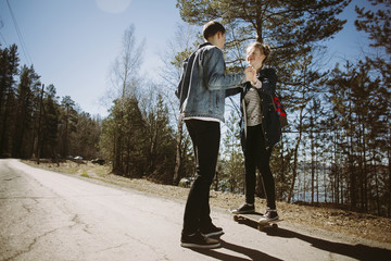 Low angle view of couple holding hands on country road during summer