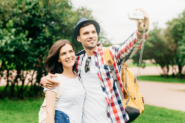 Portrait of happy family couple having walk outdoors, making photo of themselves with their camera, enjoying good weather, embracing each other. Attractive male and female photographing together