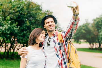 Beautiful brunette female standing close to her husband, posing in camera while making selfie, having joy together while spending their vacations in big city, exploring new places of interest