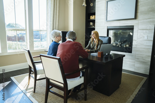 Senior Couple Discussing With Financial Advisor While Sitting In Office