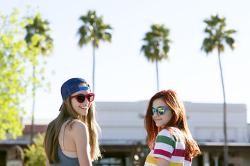 Portrait of happy female friends in sunglasses looking over shoulder