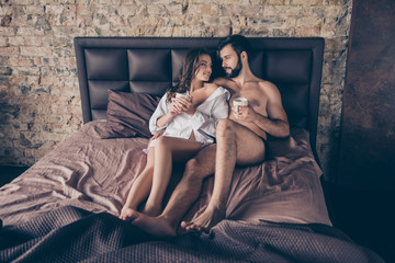 Young naughty lady with her lover in bed, so relaxed and calm, having mug of hot coffee. Bearded brunet lover looks at his gorgeous young lady lying in his white classic shirt, enjoying
