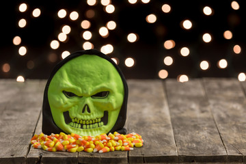 green skull with halloween candy on wooden board