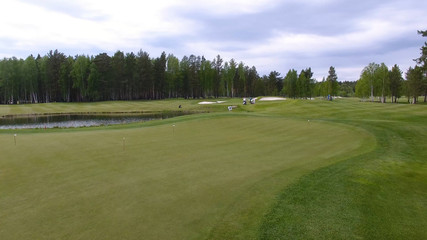 Golfers hitting golf shot with club on course while on summer vacation, aerial
