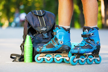 Closeup photo of legs in blue inline skates standing.