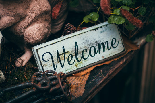 vintage welcome sign on table with iron key