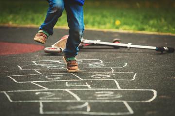 little boy playing hopscotch on playground