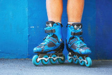 Closeup photo of legs in blue inline skates standing against blue wall.