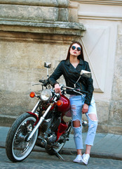 Stylish woman in leather jacket on classic motorcycle in old town