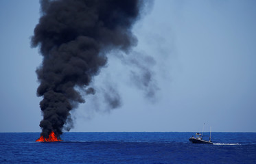 Libyan Coast Guard burns a rubber boat at the end of SAR operation headed by the SOS Mediterranee organisation with the MV Aquarius in the Mediterranean Sea