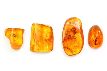 four pieces of amber with different inclusions,  beetle,  fly,  mosquito,  ant,  larva. Several pieces of amber on a white background. Sunstone with insects . Ancient insects inside fossil pitch.