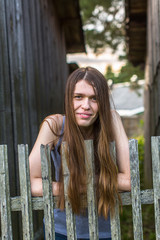 Attractive young long-haired woman standing near a wooden fence.