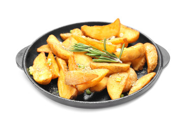 Frying pan with delicious baked potato wedges on white background