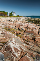 The small church of Port-au-Persil behind the rocks at low tide, Québec, Canada