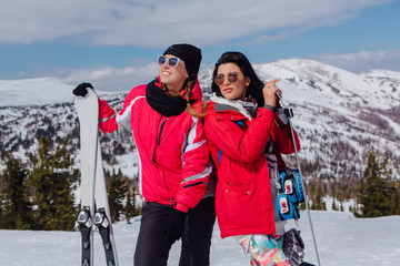 Two youn women with ski and snowboard
