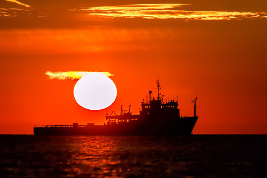 Land of midnight sun. Full sun and orange sky over tropical Eastern waters of the Orient.
