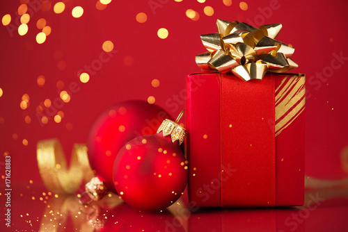 Red Gift Box With Ornaments And Ribbons On Red Holiday