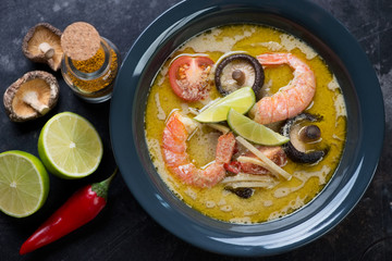 Top view of green curry thai soup with shrimps and shiitake, horizontal shot