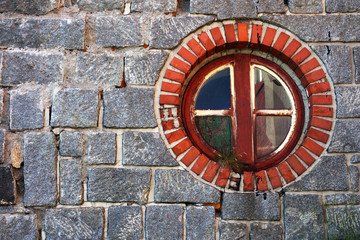 A round window on the stone wall of a building