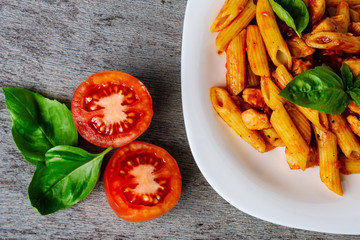 Penne with tomato sauce and basil on wooden background, top view.