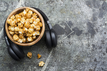 Gray grunge working stone table with laptop, headphones, wooden bowl with caramel popcorn. Modern youth grunge trends. Top View.