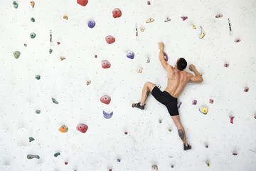Free climber exercise on a colorful indoor boulder