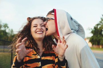 A young couple wearing animal onesies
