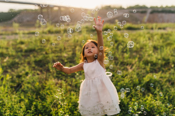 Cute little girl playing with bubble
