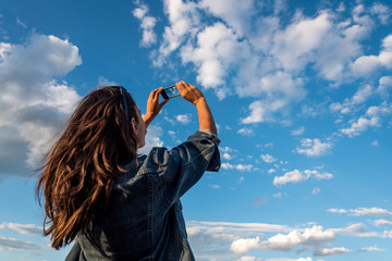 Beauty young woman taking pictures of a cloudy sky with a smartphone