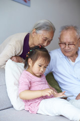 asian senior couple watch their great granddaughter using tablet