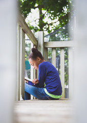 Preteen girl reading a book while sitting on the top of a outdoor playset