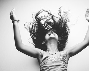 A young happy child throwing her hair.