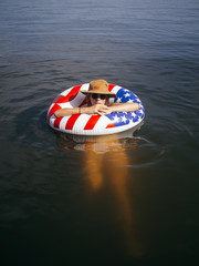 Girl relaxing in water on American Flag float