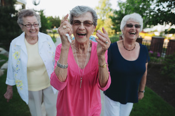Group of happy caucasian seniors walking and talking outside garden path