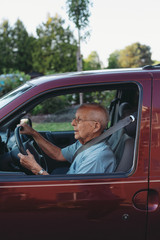 Concentrating senior man driving minivan