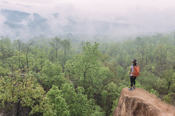 Hiker wearing backpack looking a misty mountain view
