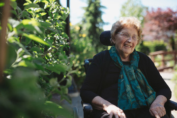 Smiling, caucasian senior woman outside in wheelchair