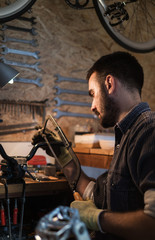Young man working on part for his bike in small rustic workshop