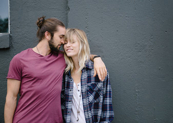 Couple standing by wall being intimate